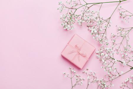 선물 또는 선물 상자와 위에서 핑크 테이블에 꽃. 파스텔 색상입니다. 인사말 카드. 플랫 레이 스타일.
