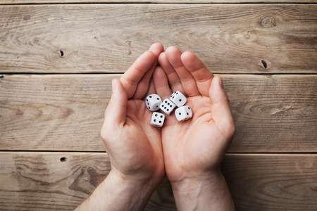 games of chance: Man holding in hand white dice over the wooden table top view. Gambling devices. Game of chance concept.