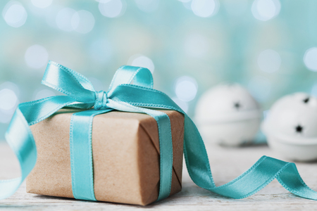 jingle bell: Christmas gift box and jingle bell against blue bokeh background. Holiday greeting card. Stock Photo