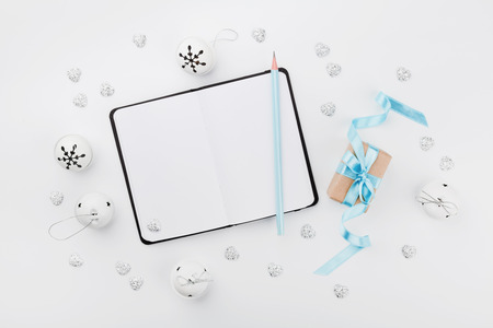 composition notebook: Christmas gift box with blue ribbon, empty notebook and jingle bell on white table from above. Holiday greeting card. Mockup. Flat lay composition. Stock Photo