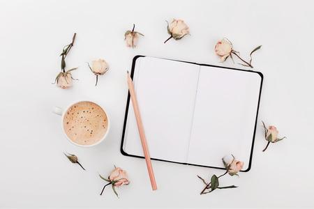 La taza de café de la mañana, el cuaderno vacío y las rosas secas florece en la tabla blanca desde arriba. Acogedor desayuno. Estilo plano de la endecha