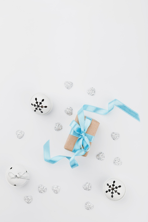 blue gift box: Christmas gift box with blue ribbon and jingle bell on white background from above. Holiday greeting card. Mockup. Flat lay composition. Stock Photo