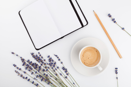 Coffee, clean notebook and lavender flower on white  background from above. Woman working desk. Cozy breakfast. Mockup. Flat lay style. Standard-Bild