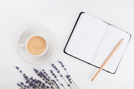 Café, cuaderno limpio y flor de la lavanda en la tabla blanca desde arriba. Escritorio de trabajo de mujer. Acogedor desayuno Bosquejo. Estilo plano de la endecha Foto de archivo - 68999145