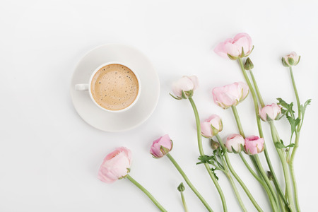 Beautiful spring Ranunculus flowers and cup of coffee on white desk from above. Greeting card. Breakfast. Pastel color. Clean space for text. Flat lay style. Stock Photo