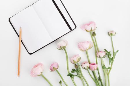 Mooie de lenteranunculus bloemen en leeg notitieboekje op witte lijst van hierboven. Mockup. Pastelkleur. Maak ruimte vrij voor tekst. Vlakke lay-stijl. Stockfoto