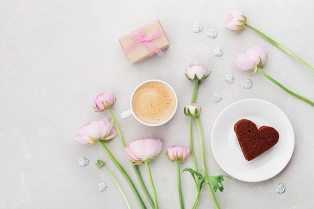 Breakfast for Valentines day with cup of coffee, gift, flowers and cake in shape of heart on gray table from above in flatlay style. Stock Photo