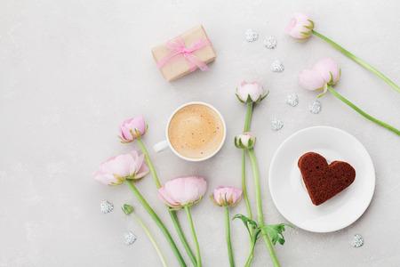 Ontbijt voor Valentijnsdag met een kopje koffie, cadeau, bloemen en cake in de vorm van hart op grijze tafel van bovenaf in flatlay stijl.
