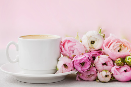 Beautiful spring Ranunculus flowers and cup of coffee on gray stone table. Pastel color. Greeting card for Valentines or Womans Day. Breakfast. Empty space for text.
