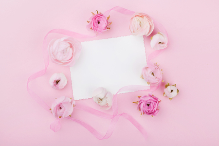 White paper blank and spring flower on pink desk from above for wedding mockup or greeting card on womans day. Floral frame in flat lay style.