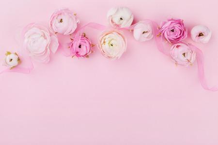 結婚式のモックアップや梨花の日にグリーティング カードの上からピンクの机の上の美しい春の花。フラット レイアウト スタイルで花の境界線。 写真素材