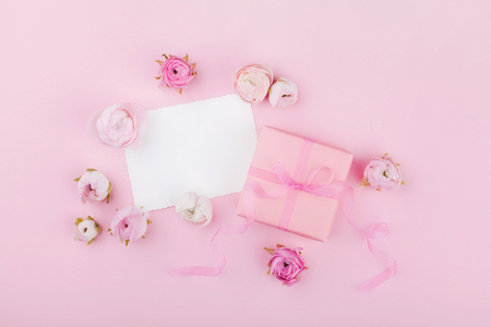 Gift or present box, white paper blank and spring flower on pink desk from above for wedding mockup or greeting card on womans day in flat lay style.