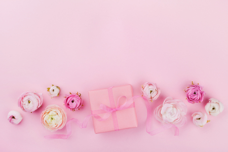 Gift or present box and beautiful spring flower on pink desk from above for wedding mockup or greeting card on womans day in flat lay style.