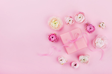 Gift or present box and beautiful flower on pink desk from above for wedding mockup or greeting card on womans day in flat lay style.