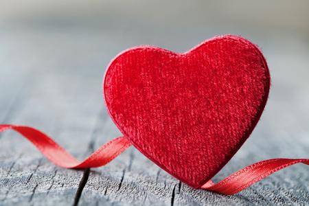 Tarjeta de felicitación en el día de San Valentín con par de corazón rojo sobre fondo de madera rústica.