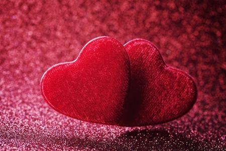 Tarjeta de felicitación en el día de San Valentín con par de corazón rojo en el fondo del bokeh.