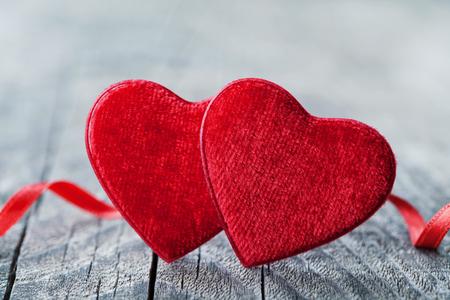 Tarjeta de felicitación en el día de San Valentín con par de corazón rojo sobre fondo de madera.