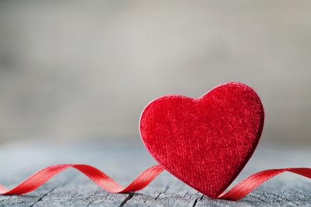 Tarjeta de felicitación en el día de San Valentín con par de corazón rojo sobre fondo de madera de la vendimia. Foto de archivo