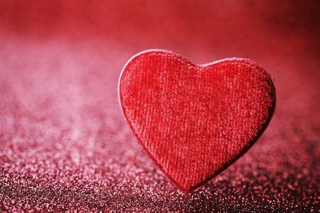 Tarjeta de felicitación en el día de San Valentín con el corazón rojo en el fondo del brillo. Foto de archivo