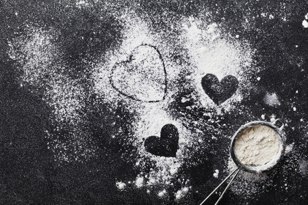 form: Baking background with flour and heart shape on kitchen black table from above for Valentines day cooking. Flat lay style.
