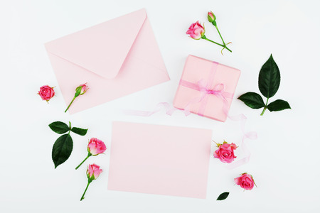 greeting card: Gift or present box, envelope, paper blank and pink rose flower on white table top view in flat lay style for greeting card on Womans day.