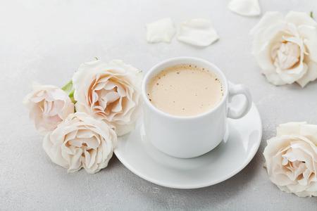 rosas blancas: Taza de café y flores color de rosa del vintage por buenos días en la tabla de piedra gris. Hermoso desayuno en las madres o día de la mujer.