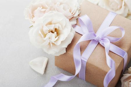 Vintage rose fleurs et coffret cadeau avec un ruban arc sur table lumineuse. Carte de voeux pour l'anniversaire, Womans ou la fête des mères.