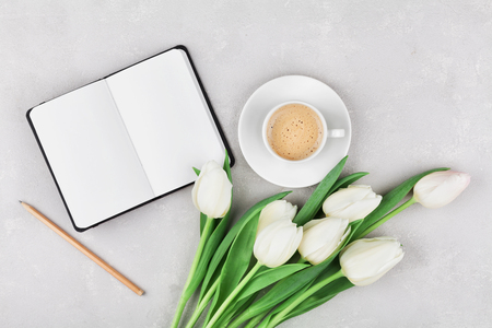 woman working desk with coffee mug notebook and spring tulip flowers top view in flat lay style