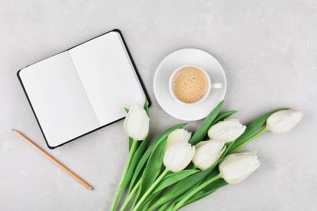madre trabajando: Mujer mesa de trabajo con la taza de café, portátiles y flores de primavera de tulipanes vista desde arriba en estilo aplanada. Foto de archivo