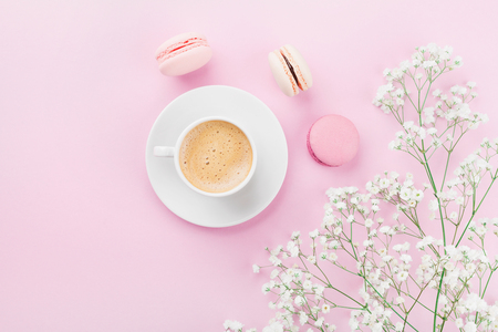 Morning cup of coffee, cake macaron and flowers on pink table top view in flat lay style. Beautiful breakfast for woman.