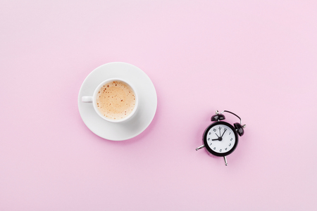 Morning cup of coffee and alarm clock on pink working desk top view in flat lay style. Stockfoto