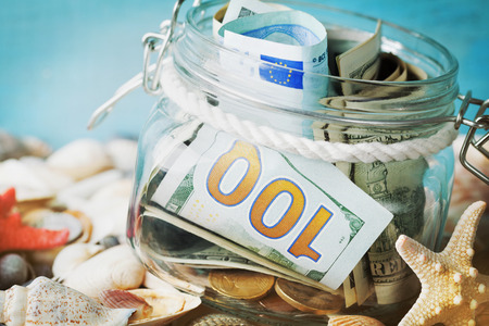 Money in glass jar on blue background. Savings for summer holidays, vacation, travel and trip. Stock Photo