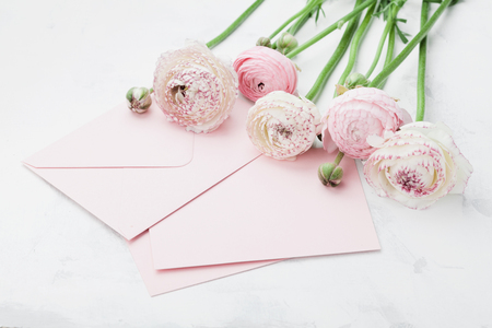 Envelope or letter, paper card and pink ranunculus flowers on white table for greeting on Mother or Woman Day. Can be used as wedding mockup.