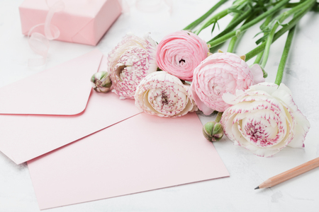 Envelope or letter, paper card, gift and pink ranunculus flowers on white table for greeting on Mother or Woman Day. Can be used as wedding mockup. Stock Photo