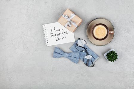 Happy Fathers Day background with morning coffee cup, gift, glasses and bowtie on stone gray desk top view in flat lay style.