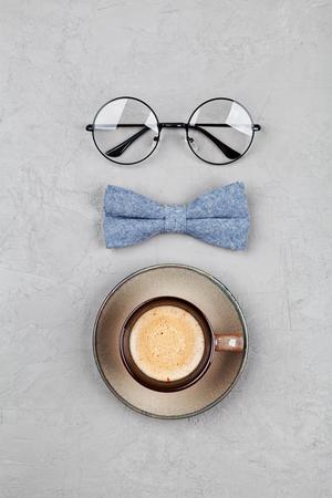 愉快的父亲节背景与早晨咖啡杯,玻璃和bowtie在石灰色桌顶视图在平的放置样式。