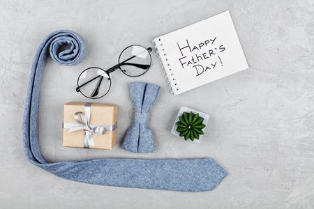 De gelukkige achtergrond van de Vadersdag met notitieboekje, gift, glazen, stropdas en bowtie op de bovenkantmening van de steenlijst in vlakte legt stijl.