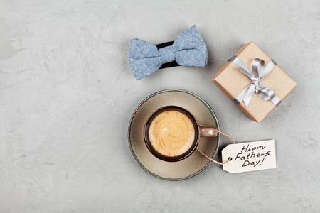 Morning cup of coffee, gift and bowtie on stone table top view in flat lay style for breakfast on Happy Fathers Day.