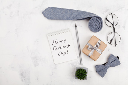 Happy Fathers Day background with notebook, gift, glasses, necktie and bowtie on white table top view in flat lay style.