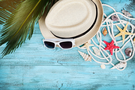 exotics: Straw hat, sunglasses, palm leaves, rope, seashell and starfish on turquoise wooden table top view in flat lay style. Summer holidays, travel and vacation background.