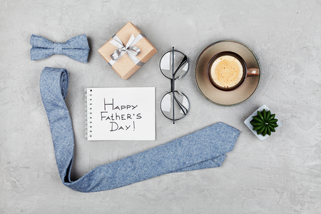 Happy Fathers Day background with morning coffee mug, gift, glasses, necktie and bowtie on stone table top view in flat lay style. Foto de archivo