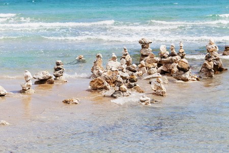 water wave: Stone tower against blue sea for balance, meditation and zen theme.