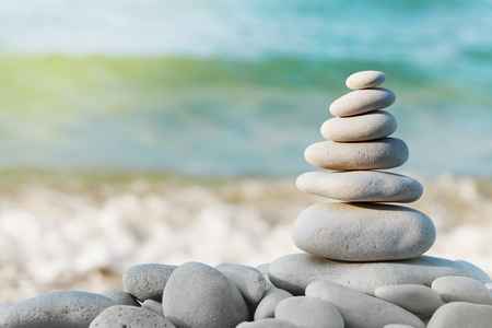 Stack of white pebbles stone against blue sea background for spa, balance, meditation and zen theme. Imagens