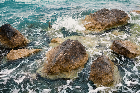 Dramatic view of stones or rocks washed by the turquoise sea water.