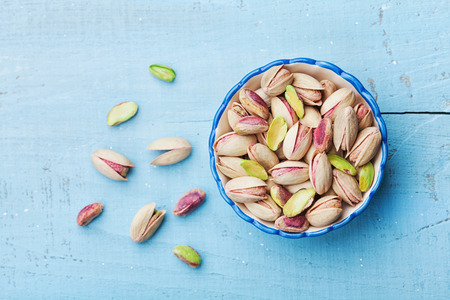 Bowl of pistachio nuts on blue rustic table top view. Healthy food and snack.