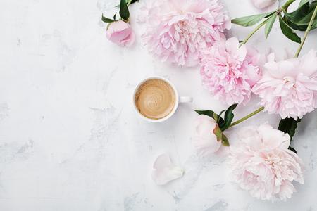 Café de la mañana y hermosas flores de peonía rosa en la vista de mesa de piedra blanca en estilo plano. Acogedor desayuno en el día de la Madre o Mujer.
