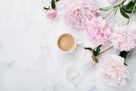Morning coffee and beautiful pink peony flowers on white stone table top view in flat lay style. Cozy breakfast on Mother or Woman day. Stockfoto