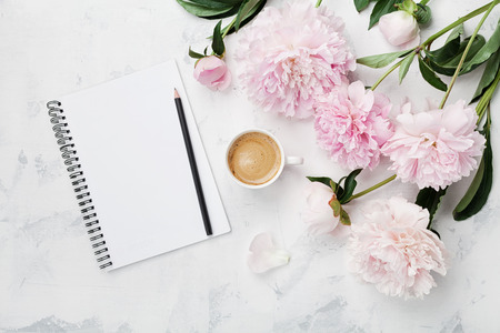 Morning coffee mug for breakfast, empty notebook, pencil and pink peony flowers on white stone table top view in flat lay style. Woman working desk. Stockfoto