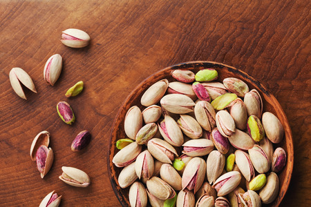 Bowl of pistachio nuts on wooden rustic table top view. Healthy food and snack.