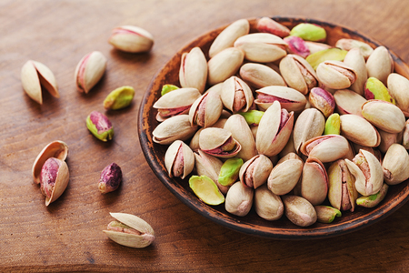 Bowl of pistachio nuts on wooden rustic table. Healthy food and snack.  Stock Photo